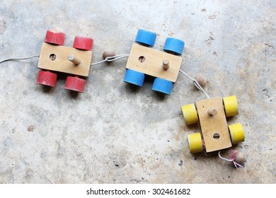 Old colorful wooden toy train on concrete floor