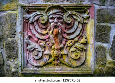 Old and colourful waterspout made of stone looking like a face