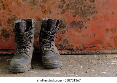 Old Combat boot on rusty red background