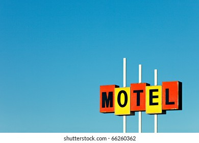 An old commercial motel sign against a clear blue sky.