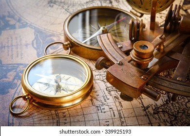 Old compass, astrolabe on vintage map. Retro stale. Very shallow focus.