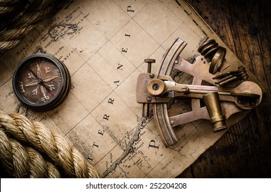 Old compass, astrolabe and rope on vintage map. Adventure stories background.
