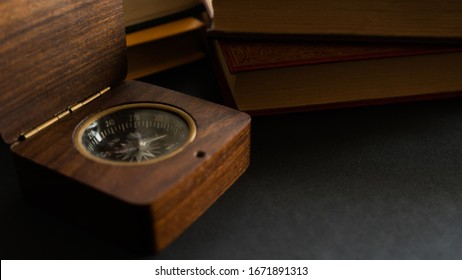 old compass close up with books