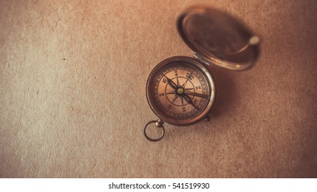 Old compass collection on brown paper background. (vintage style)