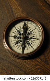 Old compass on the background of brown boards