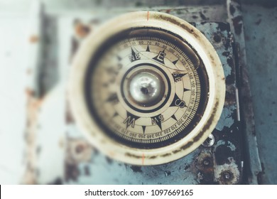 Old compass on a boat showing direction. Selective focus with wooden background vintage color.Thailand
