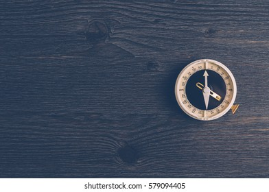 Old compass on a dark wooden background. The concept of direction or travel