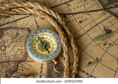 Old compass on vintage map with rope closeup. Retro stale