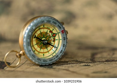 Old compass on vintage map. Retro stale