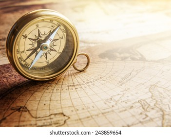 Old compass on vintage map. Retro stale.