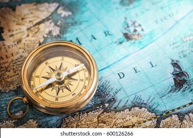 Old compass on vintage map. Adventure stories background. Retro style