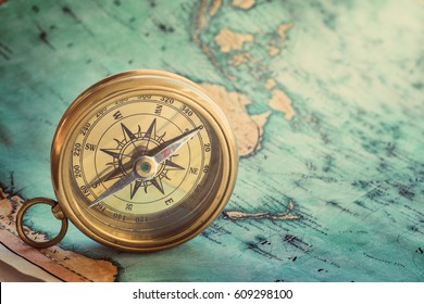 Old compass on vintage map. Adventure stories background. Retro style.