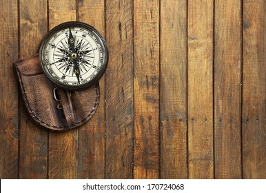 Old compass on wooden background with space for text