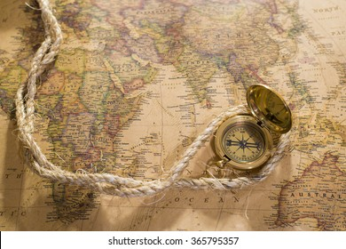 old compass and rope on vintage map