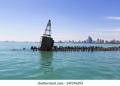 old concrete buoy on breakwater with Chicago skyline