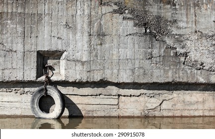 Old concrete mooring wall with automotive tire hanging on chain as a bumper