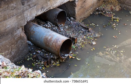 Old Concrete and rusty metal, cast-iron drainage pipes and soil on construction site. Consolidated wastewater system, leveled in place. Repair Drainage trench of rainwater drainage system