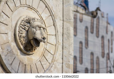 old concrete and stone sculpted feature of a lions head gazing out with fierce eyes