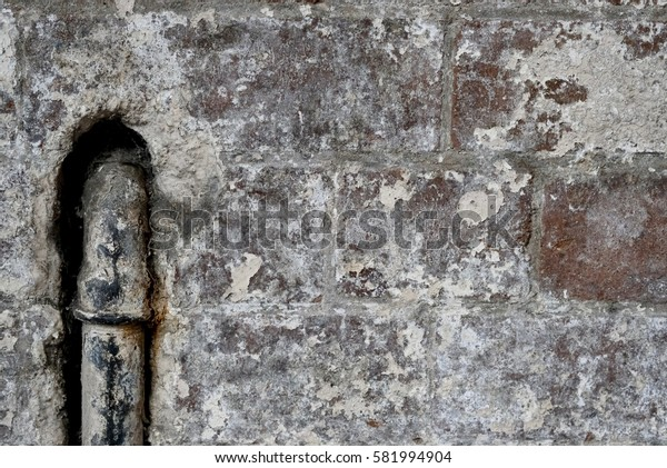 Old concrete wall background with metal pipe.