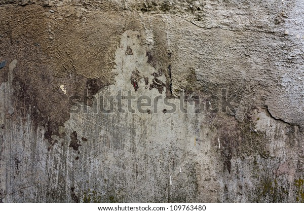 Old concrete wall covered with destroyed paint and plaster