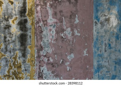 An old concrete wall painted yellow, pink and blue