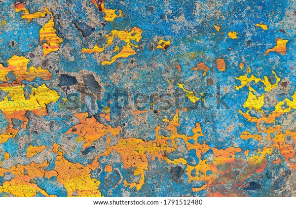 Old concrete wall with remnants of bright paint. Colors - blue, yellow, orange. Peeling, cracking, weathering.