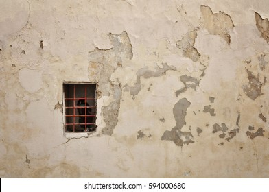 Old concrete wall with window bars