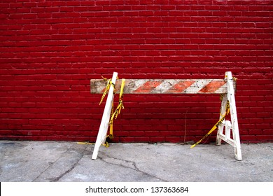 Old Construction Barrier Sawhorse on a sidewalk against a Red Brick Wall