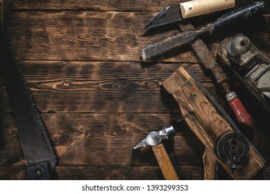 Old construction tools on a wooden workbench flat lay background with copy space. Carpenter table. Woodwork.