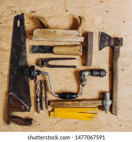 Old construction tools on a wooden workbench flat lay background. Carpenter table. Woodwork