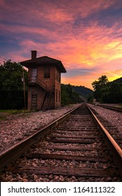 An old control tower along train tracks at sunset