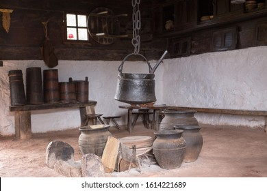 Old cooking cauldron and clay vessels on fireplace in cottage
