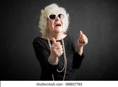 Old and cool woman showing both thumbs up