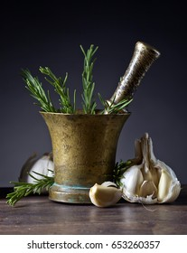 Old copper mortar with rosemary and garlic on a wooden table .