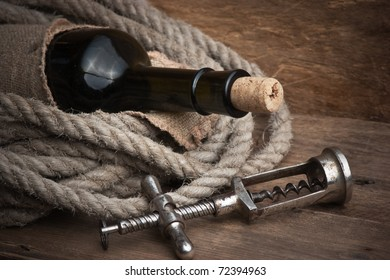 Old corkscrew and bottle of wine on the board