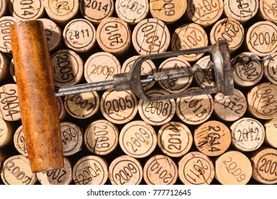 Old corkscrew in retro look lies on a background of many vintage corks
