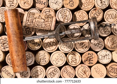 Old corkscrew in retro look and a wine cork are lies on a background of many vintage corks