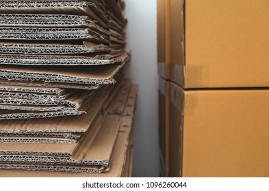 Old corrugated cardboard boxes stacked close to new brown carton boxes stacked
