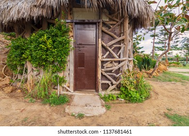 Old cottage made of tree trunks with closed wooden brown grunge door and thatch roof, surrounded by green bushes at Montaza public park, Alexandria, Egypt
