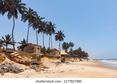 Old cottages and palm trees on Sankofa beach Ghana, near Accra city
