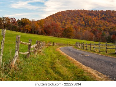 An old country road lined with a split rail fence turns as the autumn leaves glow with color against the North Carolina sky.
