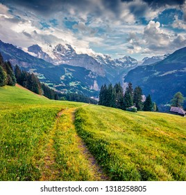 Old country road on the mountain valley. Dramatic summer view of Wengen village. Nice morning scene of countryside in Swiss Alps, Bernese Oberland in the canton of Bern, Switzerland, Europe.