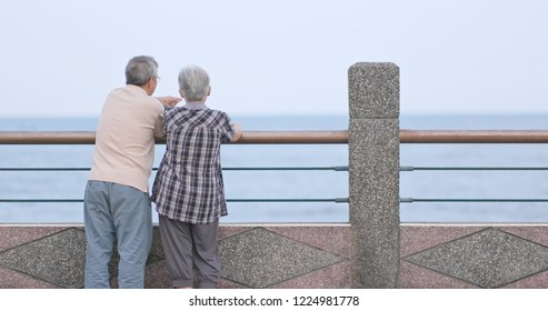 Old couple chatting and looking at the sea together
