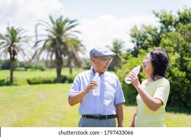 Altes Ehepaar trinkt Wasser draußen