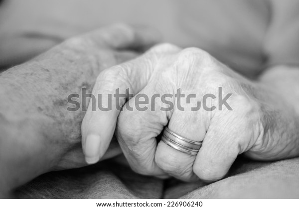 Old couple friendship holding hand, close-up in black and white