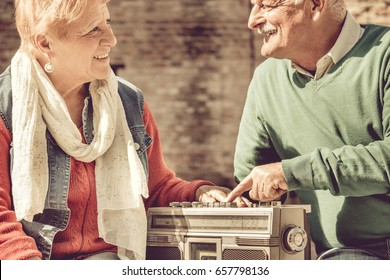 old couple happy retirement. elderly man and woman enjoy listening to evergreen music on vintage radio.