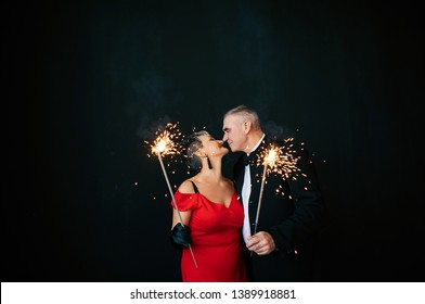 old couple in love - a woman in a red dress and a gray-haired man in a black suit on the anniversary of their wedding burn fireworks and lights and passionately embrace