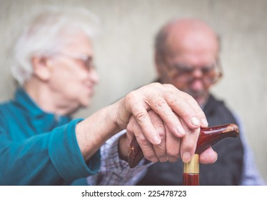 old couple. old man an woman still together holding each other hands over the man cane