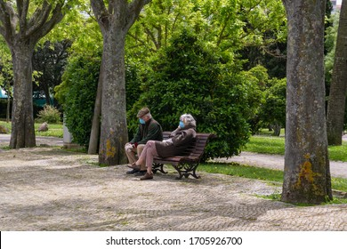 Old couple with masks sitting in the park during coronavirus. Older people during epidemic with masks  on the banch in Lisbon 13.04.2020