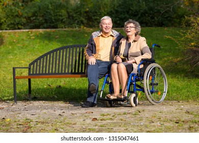 old couple in the park - woman sitting on wheelchair and man on a bench